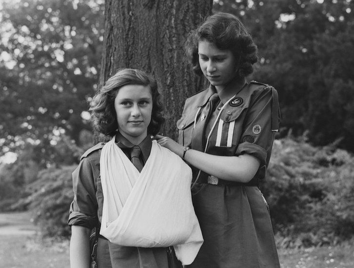 Princess Elizabeth places Princess Margaret's arm in a sling as part of the girl guides in Frogmore, Windsor, England on 11 April 1942
