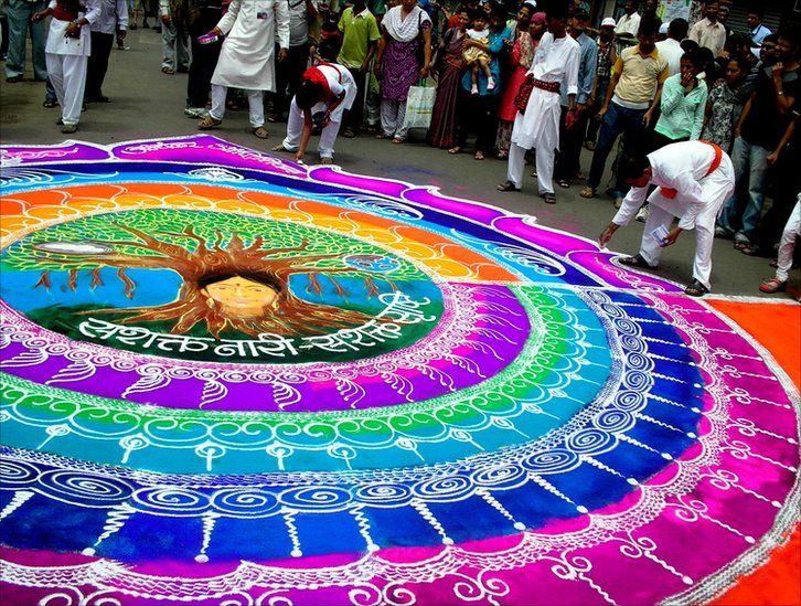Artists creating designs in coloured powder on the streets of Pune, India during the immersion procession of the annual Ganesha Festival
