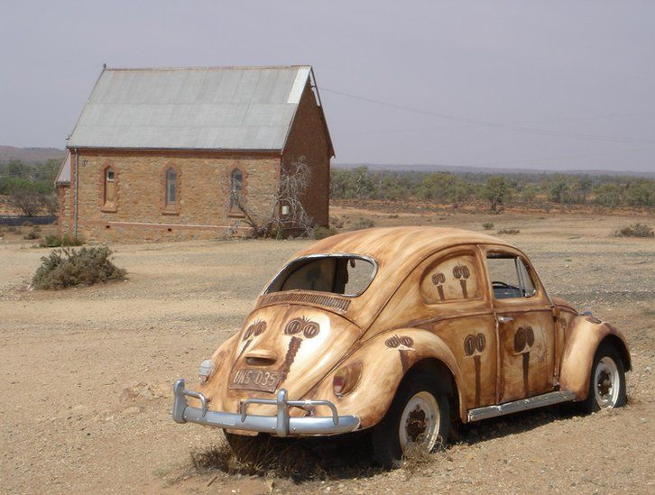 A VW Beetle next to a building