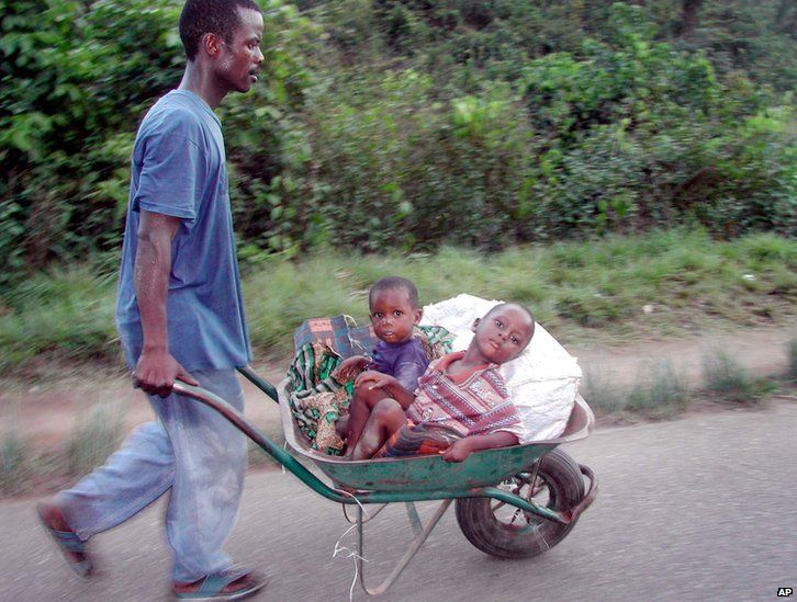 Liberian civilians flee the ongoing fighting between Liberians United for Reconciliation and Democracy (LURD) rebels and government troops in Gbarnga, Liberia, 24 March 2003