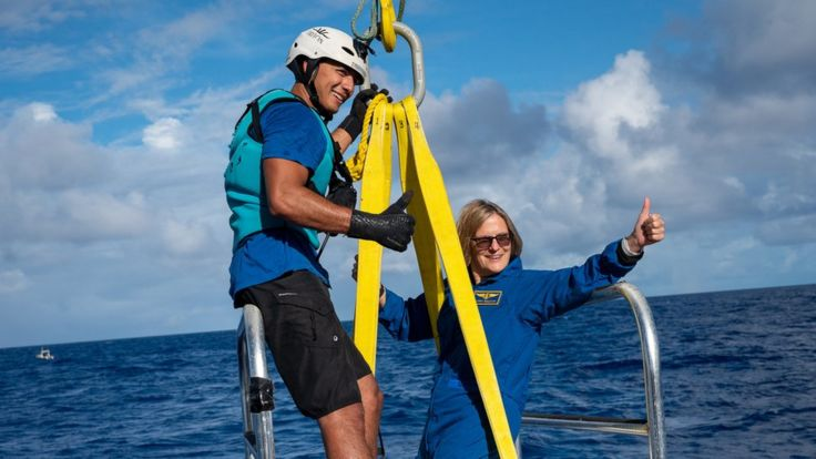 Dr Sullivan hanging from a winch over the ocean