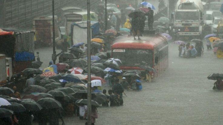Residentes de la ciudad de Mumbai caminan en una calle inundada entre vehículos que no pueden avanzar por el agua.