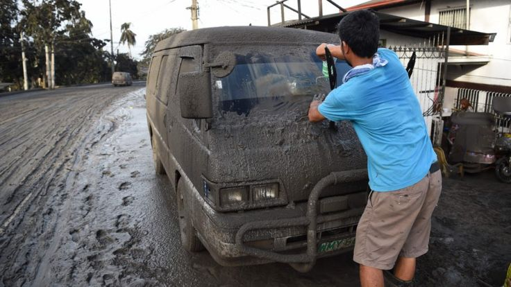 A resident cleans mud and ash from his car