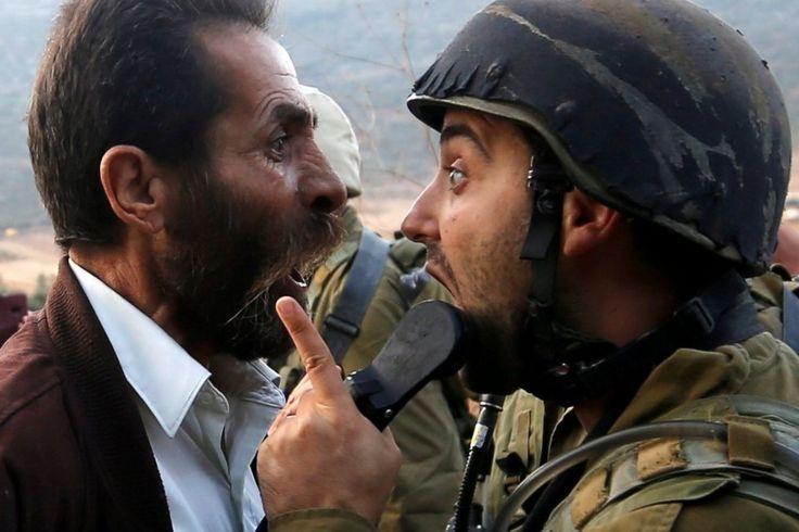 A man argues with a soldier