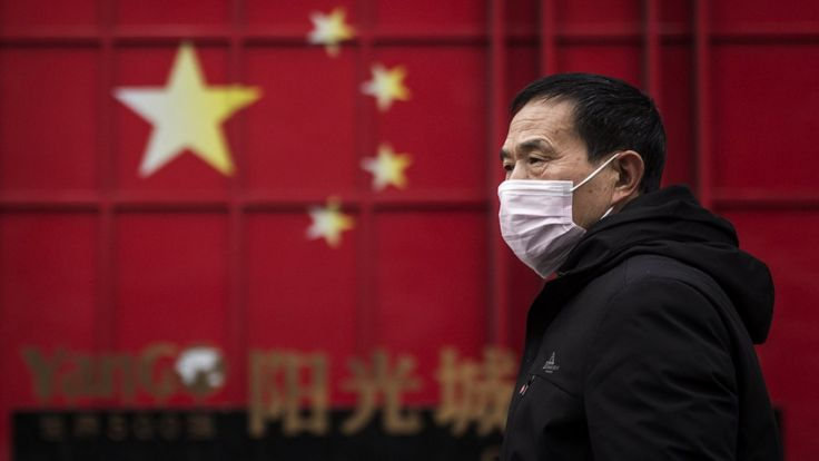 Homem anda de máscara em Wuhan