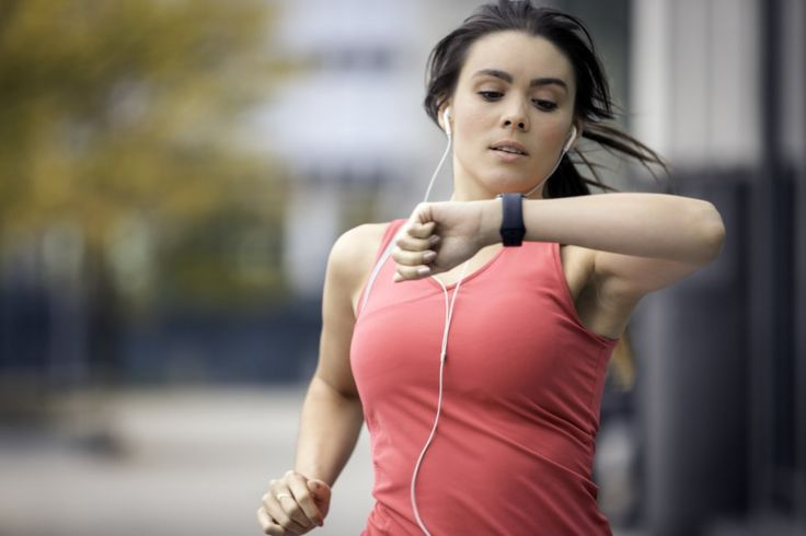 Woman jogging and looking at fitness band