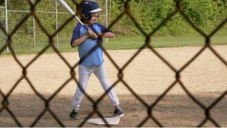 Girl playing baseball, with fencing