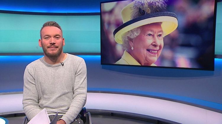 Martin on the Newsround set with a picture of the Queen
