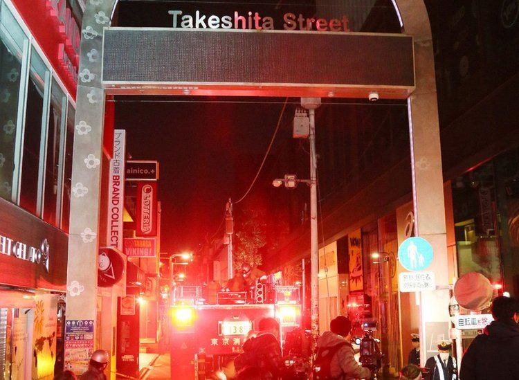 Takeshita Street sign with ambulance in the background