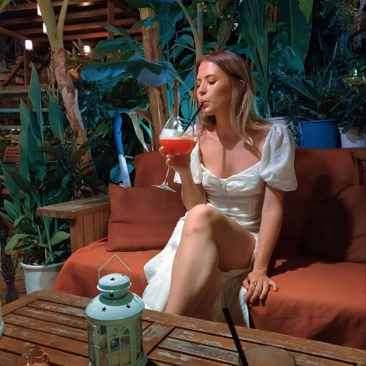 Fashion graduate Lucy sips a cocktail wearing a long white dress with a slit