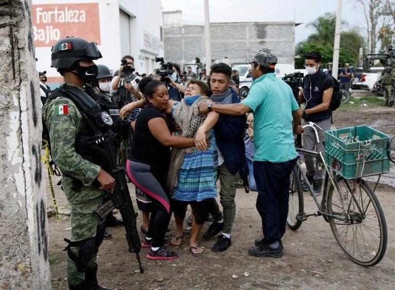 A woman reacts near the crime scene where 24 people were killed in Irapuato, Guanajuato state, Mexico, on July 1, 2020.