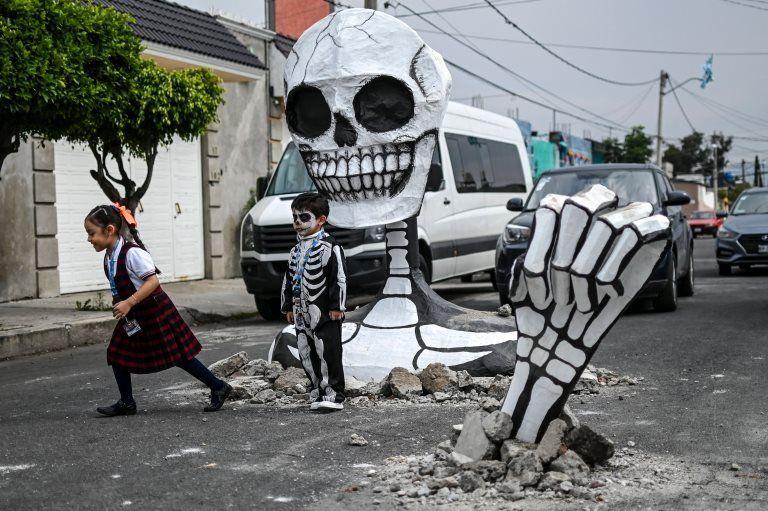 Children pose next to the cardboard skeleton