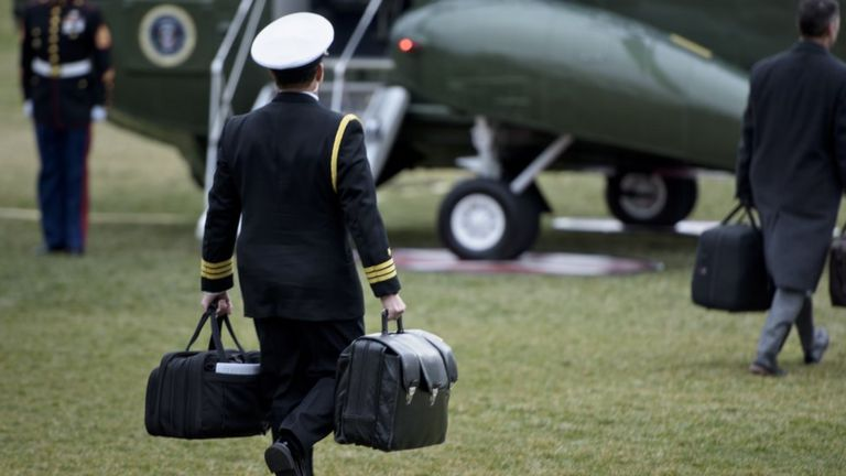 Military officer carries two briefcases to a military aircraft on the White House lawn.