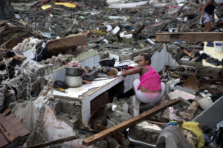 Woman searching through rubble