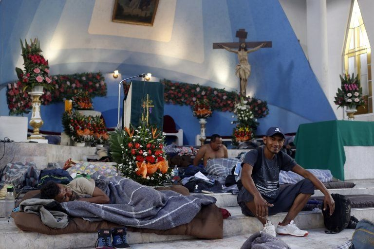 Migrants rest in a church in Puebla in Mexico