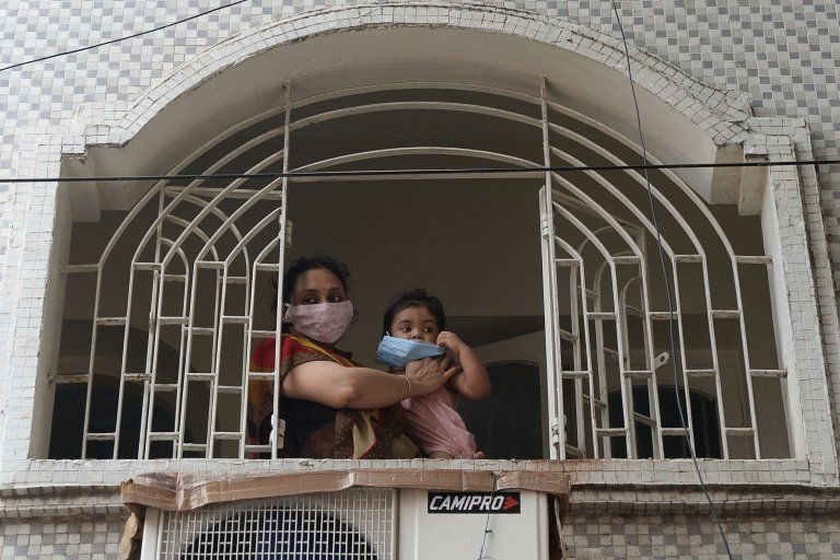 A resident along with her child wearing face mask stands in front of a window during a government-imposed nationwide lockdown in Chennai on June 29, 2020