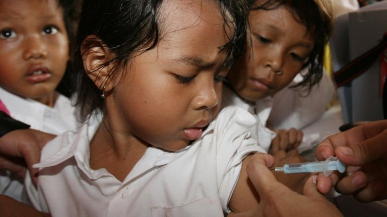 Girl watches as an adult hand administers a vaccine by needle into her upper arm. Child next to her also watches