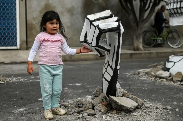 """A girl touches the """"hand"""" of a cardboard skeleton"""