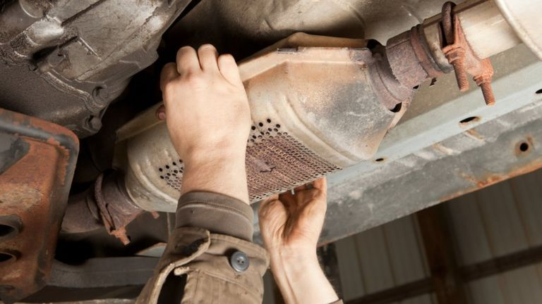 A catalytic converter being removed from an SUV.