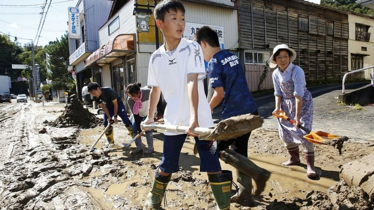 Schoolchildren and residents remove mud after flooding caused by Typhoon Hagibis in Marumori, Miyagi prefecture, Japan, October 13, 2019