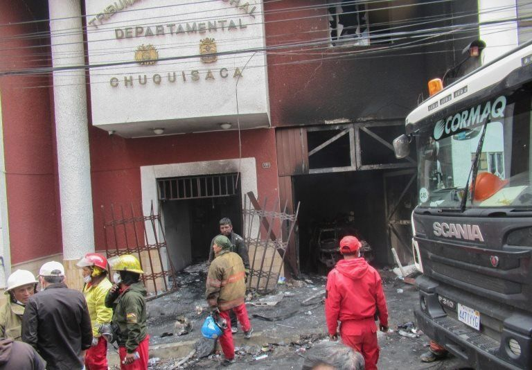 Firefighters work outside the Bolivian electoral office set on fire by protesters on 21 October, 2019.