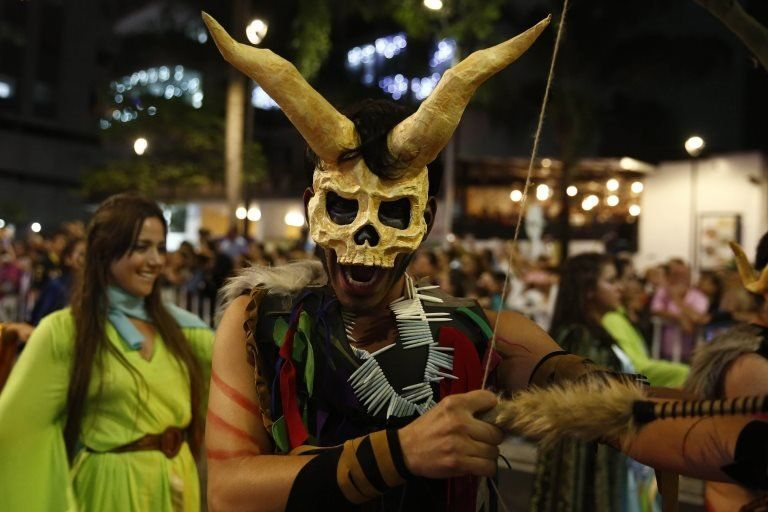 An artist wearing horn and pointing an arrow parades through Medellín
