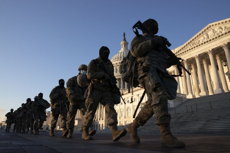Soldiers walk in a line outside the US Capitol