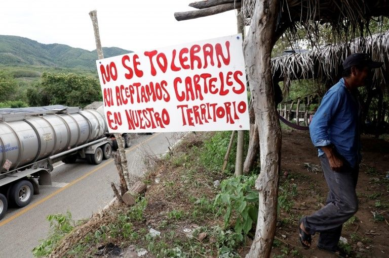 """A sign reads: """"We do not tolerate nor accept drug cartels in our territory"""" at a checkpoint in Mexico"""