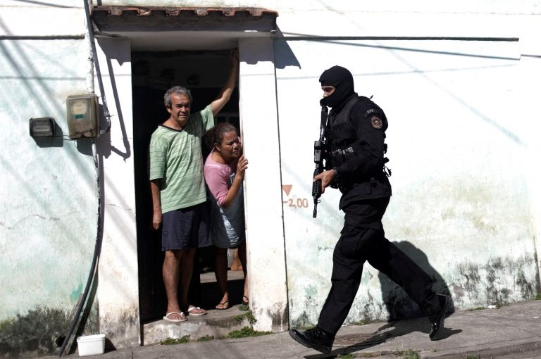 Residents look on as policemen patrol during an operation against drug dealers in Cidade de Deus slum in Rio de Janeiro, Brazil, July 10, 2017