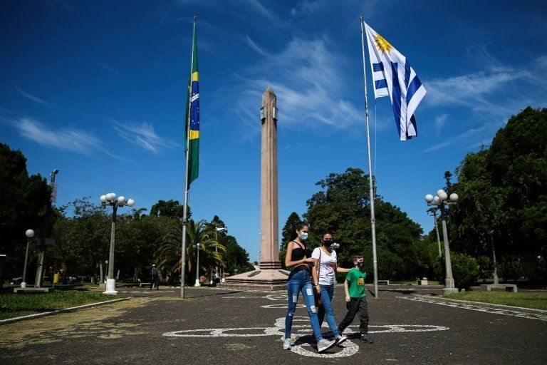 People walk on the International Square, amid the coronavirus disease (COVID-19) pandemic, at the border of Brazilian city Santana do Livramento and Uruguayan city of Rivera, Uruguay March 19, 2021