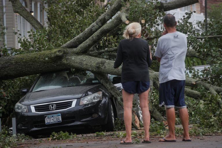 People look at a fallen tree on a car in the aftermath of Tropical Storm Isaias in the Rockaway area of Queens in New York City, U.S., August 4, 2020.