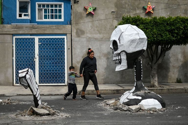 A woman and her child walk up to a cardboard skeleton in Mexico City