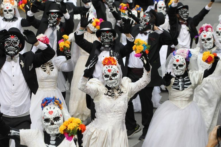 People dressed as skeletons dance during the Catrina parade in Mexico City on 27 October