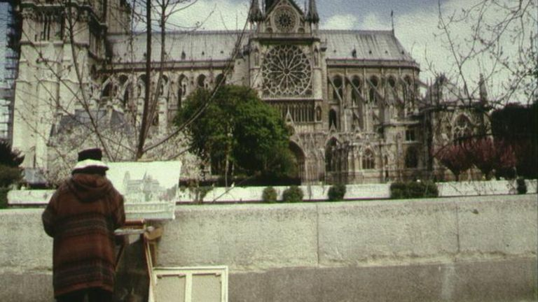 A Paris street artist paints the Notre-Dame