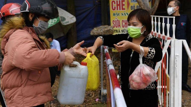 Xăng dầu được người dân Sơn Lôi mua bằng các can nhựa và chuyển qua các chốt kiểm dịch
