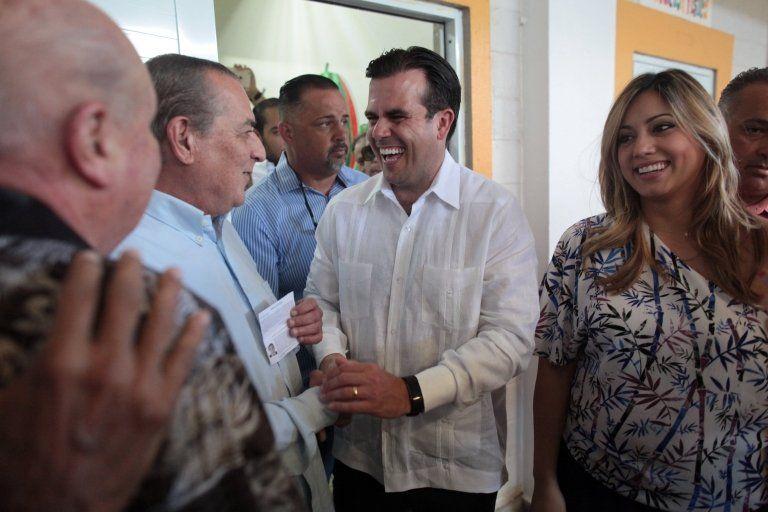 Puerto Rico Governor Ricardo Rossello (C) and his wife Beatriz Rossello (R) greet voters on 11 June, 2017.