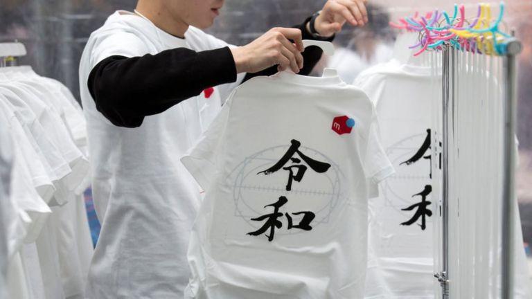 Un empleado cuelga las camisetas con los caracteres de Reiwa