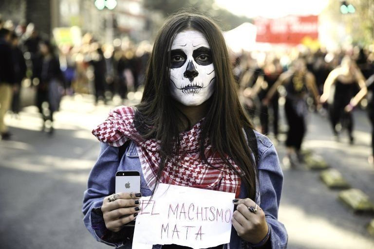 """A woman holds a sign that reads """"machismo kills"""" during a demonstration in Santiago, Chile, 06 June 2018."""