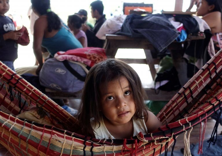 A girl rests in a hammock as her family sets up camp during the protest march.