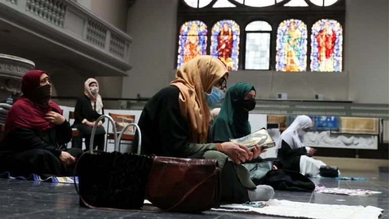Women wearing headscarves and face masks attend Friday prayers at a Berlin church