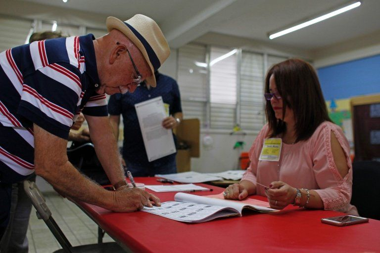 A man signs a voting list before casting his ballot during the referendum for Puerto Rico political status at a polling station in Guaynabo, on 11 June, 2017.