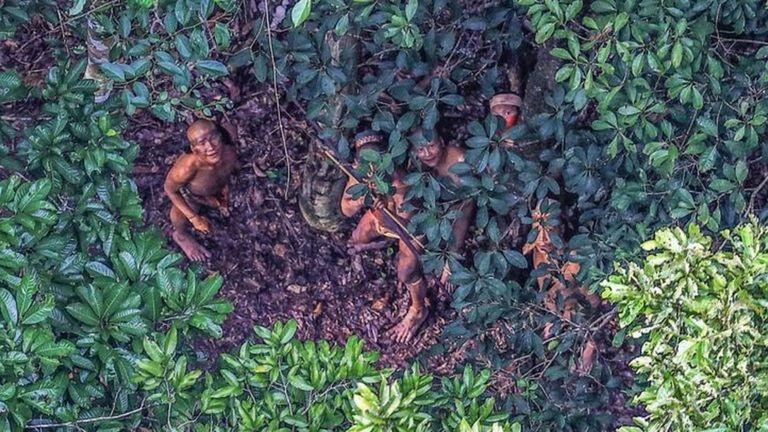Аборигены смотрят на вертолет, кружащий над их поселением