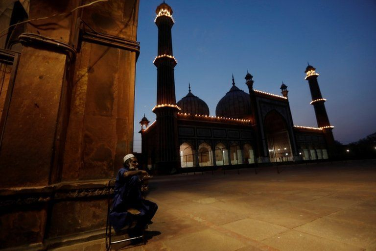 A man breaks his fast outside the empty Jama Masjid in Delhi