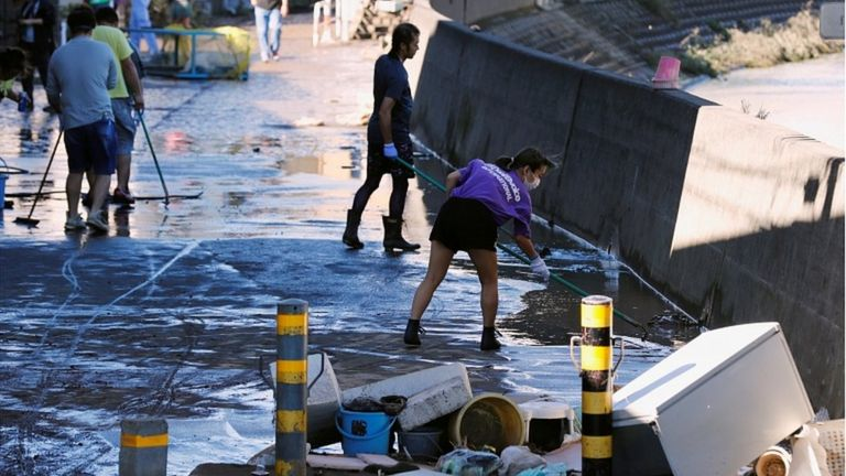 People clean up debris after floodwaters caused by Typhoon Hagibis receded in a residential area, in Kawasaki, Japan, October 13, 2019