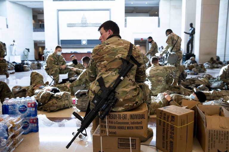 Soldiers sit inside of visitors area, sitting on supplies including water bottles