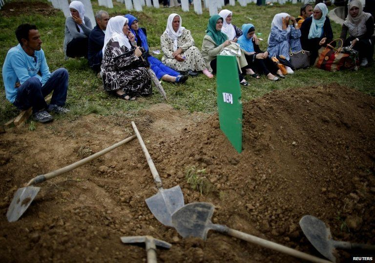 Bosnian Muslims sit near a grave after the mass funeral of 175 newly identified victims from the 1995 Srebrenica massacre, in Potocari Memorial Center, near Srebrenica, on 11 July 2014.