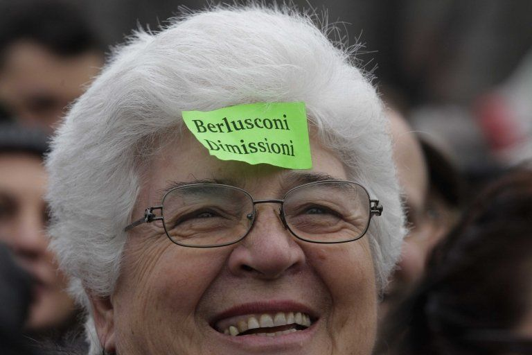 """Woman sports a sticky note against Italian premier Silvio Berlusconi reading """"Berlusconi resign"""" during a protest in Milan"""