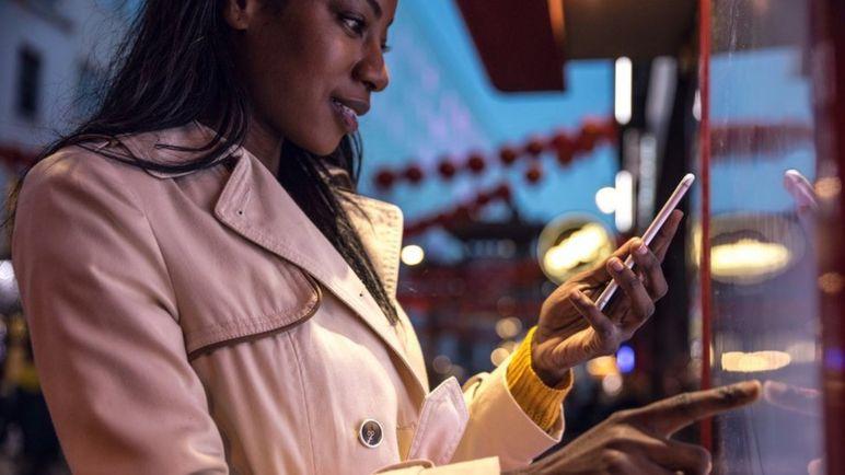 Žena na pametnom telefonu i interaktivni zaslon osjetljiv na dodir