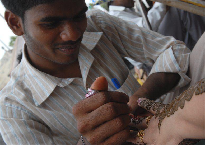 A man applies a henna design onto a woman's hand