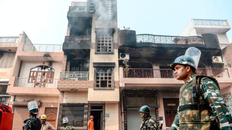 دورية أمنية تمرّ من أمام منازل محترقة ومتهدمة بعد مصادمات بين متظاهرين مؤيدين وآخرين معارضين لقانون المواطَنة الجديد في الهند، في نيودلهي في 26 فبراير/شباط 2020
